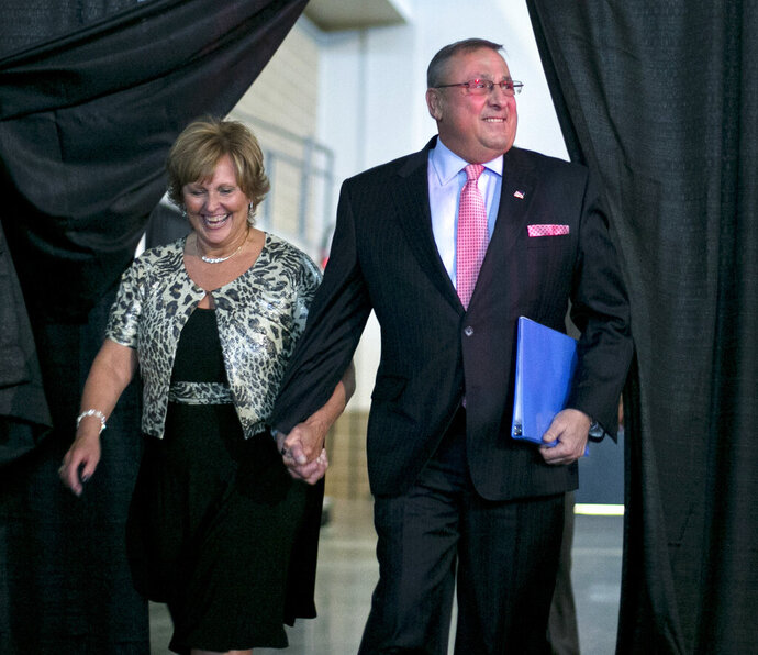 File-This April 26, 2014, file photo shows Maine Gov. Paul LePage and first lady Ann LePage arriving at the Maine Republican Convention, in Bangor, Maine. Former Republican Gov. LePage's wife won't be the only one in their family spending the summer working at a restaurant. LePage will be joining her as a bartender. McSeagulls Restaurant owner Jeff Stoddard said he hasn't finalized the former governor's schedule but expects him to be tending bar for the entire summer in Boothbay Harbor. The governor's wife, Ann, will be working there again as a server. (AP Photo/Robert F. Bukaty, File)