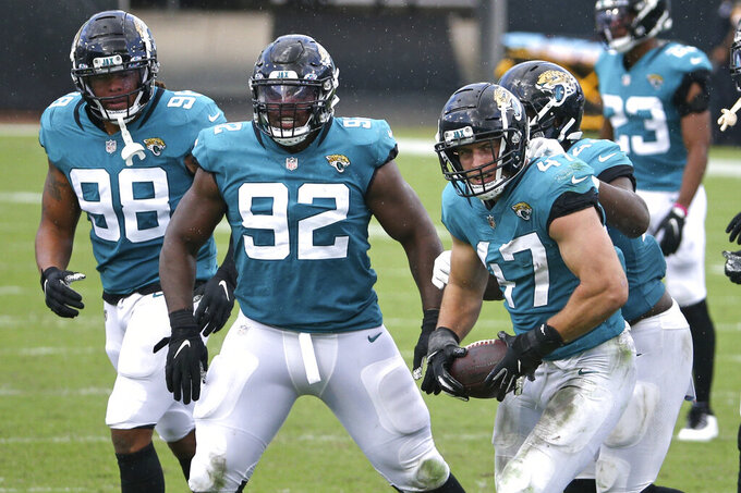 Jacksonville Jaguars linebacker Joe Schobert (47) celebrates with teammates including defensive end Jabaal Sheard (98) and defensive tackle Caraun Reid (92) after intercepting a Detroit Lions pass during the second half of an NFL football game, Sunday, Oct. 18, 2020, in Jacksonville, Fla. (AP Photo/Stephen B. Morton)