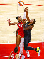 Seattle Storm's Mercedes Russell, right, shoots while being fouled by Las Vegas Aces' A'ja Wilson (22) during overtime of a WNBA basketball game at Michelob Ultra Arena on Sunday, June 27, 2021, in Las Vegas. (Chase Stevens/Las Vegas Review-Journal via AP)