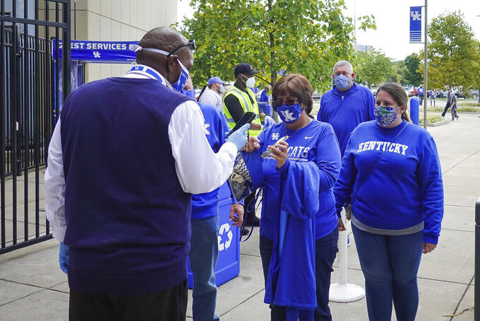 Masked Kentucky fans enter Kroger Field before during the NCAA college football game between Kentucky and Mississippi, Saturday, Oct. 3, 2020, in Lexington, Ky. (AP Photo/Bryan Woolston)