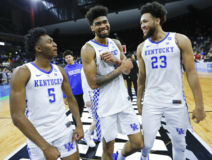 Kentucky's Immanuel Quickley (5), Nick Richards, center, and EJ Montgomery (23) smile as they leave the court after defeating Wofford in a second-round game in the NCAA men's college basketball tournament in Jacksonville, Fla., Saturday, March 23, 2019. (AP Photo/Stephen B. Morton)