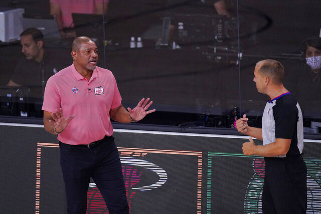 Los Angeles Clippers head coach Doc Rivers, left, questions a call during the first half of an NBA conference semifinal playoff basketball game against the Denver Nuggets, Tuesday, Sept. 15, 2020, in Lake Buena Vista, Fla. (AP Photo/Mark J. Terrill)