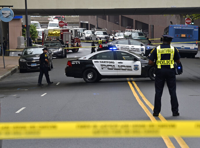 Kinsley Street in Hartford, Conn., is cordoned off after a police officer was stabbed in Spectra Boutique Apartments Thursday, May 17, 2018. A Hartford police officer responding to a disturbance was stabbed repeatedly in the neck and critically injured Thursday morning by a woman who was being evicted from an apartment building, authorities said. The police have a suspect in custody. (Brad Horrigan/Hartford Courant via AP)