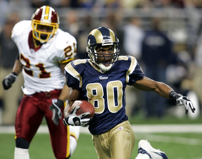 FILE - In this Dec. 24, 2006, file photo, St. Louis Rams' Isaac Bruce (80) eludes Washington Redskins Sean Taylor after making a catch during the first half of an NFL football game in St. Louis. Bruce feels the Rams set the groundwork – and the benchmark – for explosive offenses to follow. (AP Photo/Tom Gannam, File)