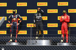 Mercedes driver Lewis Hamilton of Britain, center, celebrates his victory on the podium with second placed Red Bull driver Max Verstappen of the Netherlands, left and third placed Ferrari driver Charles Leclerc of Monaco the British Formula One Grand Prix at the Silverstone racetrack, Silverstone, England, Sunday, Aug. 2, 2020. (Ben Stansall/Poolvia AP)