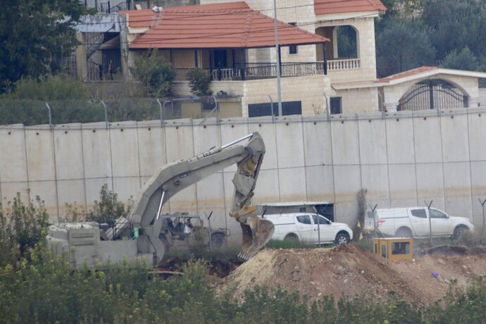 Israeli military digger works on the border with Lebanon in the northern Israeli town of Metula, Tuesday, Dec. 4, 2018. The Israeli military launched an operation on Tuesday to