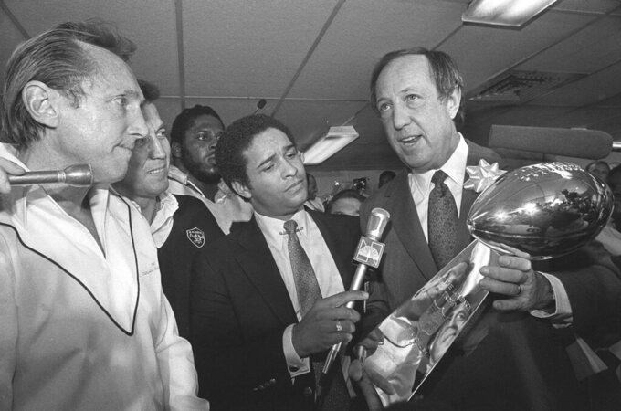 FILE - NFL Commissioner Pete Rozelle, right, presents the Super Bowl XV trophy to Oakland Raiders managing general partner Al Davis, left, as Raiders head coach Tom Flores, second from left, and sportscaster Bryant Gumbel look on after the Super Bowl in New Orleans, in this Jan. 25, 1981, file photo. When director Ken Rodgers decided to do a documentary looking back on the battles between late Raiders owner Al Davis and late NFL commissioner Pete Rozelle he decided he wanted to tell the stories from their perspectives. (AP Photo/File)