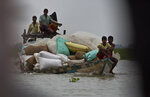 Indian villagers transport flood relief materials on a boat in Burgaon village, east of Gauhati, Assam, India, Monday, July 15, 2019. After causing flooding and landslides in Nepal, three rivers are overflowing in northeastern India and submerging parts of the region, affecting the lives of more than 2 million, officials said Monday. (AP Photo/Anupam Nath)