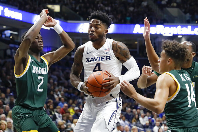 Xavier's Tyrique Jones (4) drives against Siena's Gary Harris Jr. (2) and Jordan King (14) during the first half of an NCAA college basketball game Friday, Nov. 8, 2019, in Cincinnati. (AP Photo/John Minchillo)