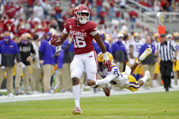 FILE - Arkansas receiver Treylon Burks (16) shakes off LSU defender Cordale Flott (25) as he runs for a touchdown during the first half of an NCAA college football game  in Fayetteville, Ark., in this Saturday, Nov. 21, 2020, file photo. Burks is the returning SEC leader in receiving yards per game after catching 51 passes for 820 yards and seven touchdowns in nine games in 2020. (AP Photo/Michael Woods, File)
