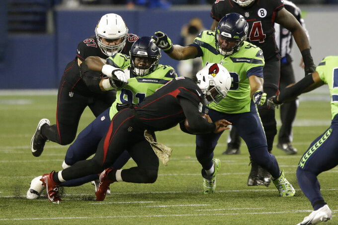 Arizona Cardinals quarterback Kyler Murray, center, is tackled by Seattle Seahawks defensive ends L.J. Collier (91) and Carlos Dunlap (43) during the first half of an NFL football game, Thursday, Nov. 19, 2020, in Seattle. (AP Photo/Lindsey Wasson)