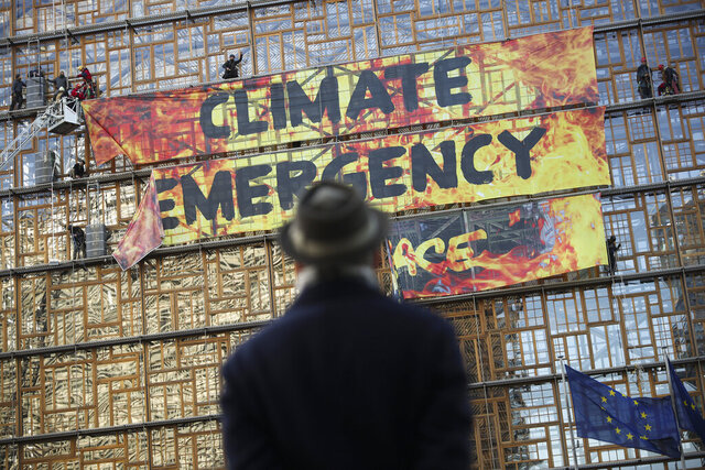 A man looks up as police and fire personnel move in to remove climate activists after they climbed the Europa building during a demonstration outside an EU summit meeting in Brussels, Thursday, Dec. 12, 2019. Greenpeace activists on Thursday scaled the European Union's new headquarters, unfurling a huge banner warning of a climate emergency hours before the bloc's leaders gather for a summit focused on plans to combat global warming.(AP Photo/Francisco Seco)