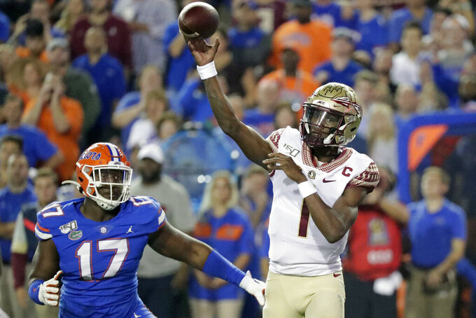 Florida State quarterback James Blackman (1) throws a pass as he is pressured by Florida defensive lineman Zachary Carter (17) during the first half of an NCAA college football game Saturday, Nov. 30, 2019, in Gainesville, Fla. (AP Photo/John Raoux)