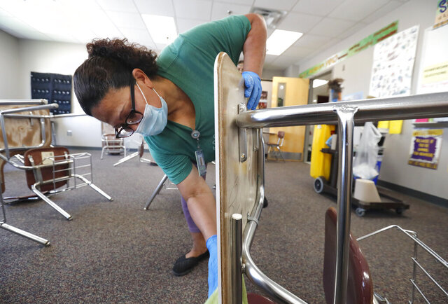 Josefina Median wears a mask as she cleans a classroom at Wylie High School Tuesday, July 14, 2020, in Wylie, Texas. (AP Photo/LM Otero)