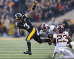 Iowa wide receiver Tyrone Tracy, left, runs for a first down and tries to elude a tackle by Minnesota linebacker Thomas Barber, center, and defensive back Jordan Howden, right, during the first half of an NCAA college football game, Saturday, Nov. 16, 2019, in Iowa City, Iowa. (AP Photo/Matthew Putney)