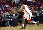 LA Clippers' Patrick Beverley, left, drives toward the basket as Houston Rockets' James Harden defends during the first half of an NBA basketball game Wednesday, Nov. 13, 2019, in Houston. (AP Photo/David J. Phillip)