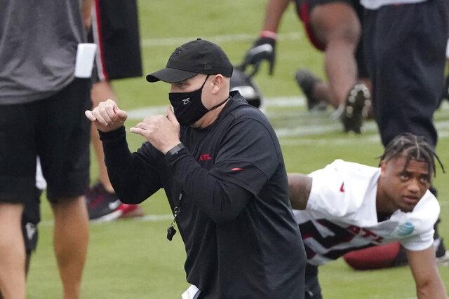 Atlanta Falcons head coach Dan Quinn shadow boxes as his team stretches during an NFL training camp football practice Sunday, Aug. 23, 2020, in Atlanta. (AP Photo/John Bazemore, Pool)