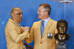 John Lynch, a member of the Pro Football Hall of Fame Class of 2021, right, is congratulated by Tony Dungy during the induction ceremony at the Pro Football Hall of Fame, Sunday, Aug. 8, 2021, in Canton, Ohio. (AP Photo/Ron Schwane, Pool)
