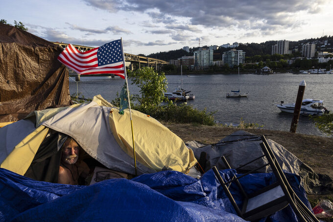 FILE - In this June 5, 2021, file photo, Frank, a homeless man sits in his tent with a river view in Portland, Ore. Portland, Oregon, has banned homeless people from camping in forested parks to both protect them from potential wildfires and prevent them from accidentally starting blazes. The City Council adopted the rule Wednesday, June 28, 2021, amid a summer of drought and record-breaking heat. (AP Photo/Paula Bronstein, File)
