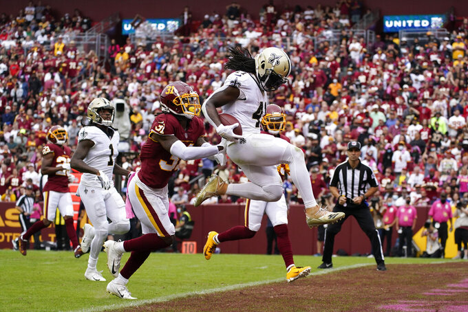 New Orleans Saints running back Alvin Kamara, right, scores a touchdown in front of Washington Football Team free safety Kamren Curl in the first half of an NFL football game, Sunday, Oct. 10, 2021, in Landover, Md. (AP Photo/Julio Cortez)