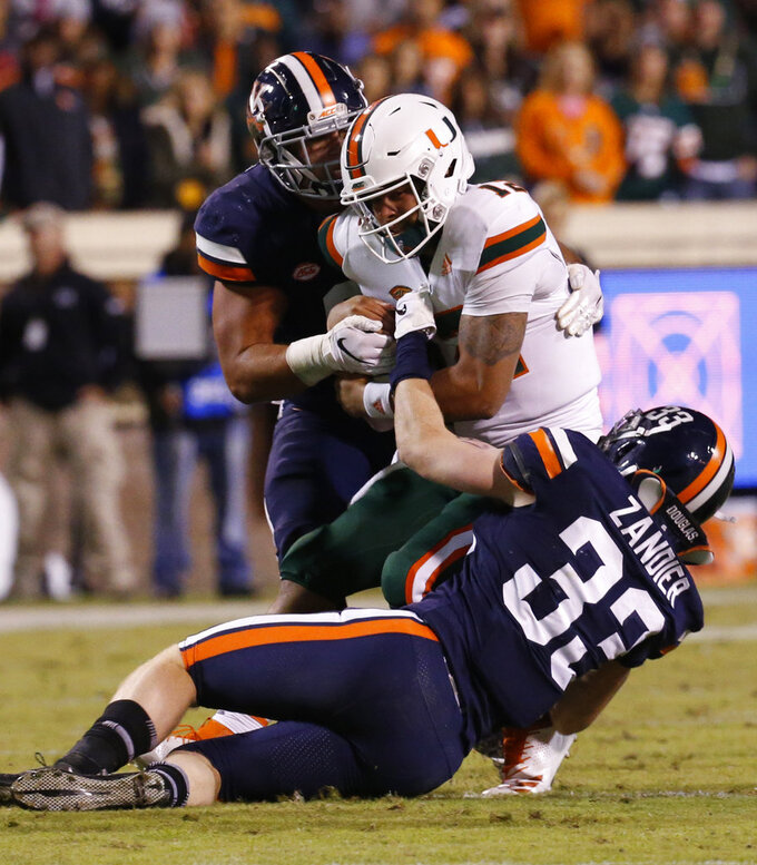 Miami quarterback Malik Rosier (12) is sacked by Virginia linebacker Zane Zandier (33) and defensive end Mandy Alonso, left, during the first half of an NCAA college football game in Charlottesville, Va., Saturday, Oct. 13, 2018. (AP Photo/Steve Helber)
