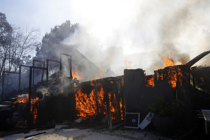 A wildfire-ravaged home burns as crews continue to battle the Getty fire Monday, Oct. 28, 2019, in Los Angeles. (AP Photo/Marcio Jose Sanchez)