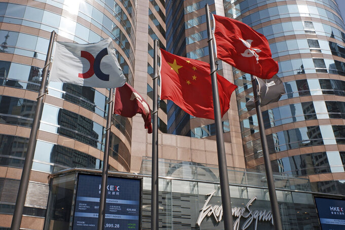 FILE - In this Oct. 9, 2019, file photo, flags are raised outside the Hong Kong Exchange Square building in Central of Hong Kong. The Hong Kong Stock Exchange said it was hit by technical problems Thursday as a wave of brief internet outages appeared to hit dozens of financial institutions, airlines and other companies across the globe. (AP Photo/Kin Cheung, File)