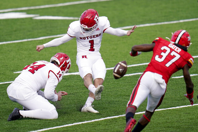 Rutgers kicker Valentino Ambrosio (1), with Zach Feagles holding, attempts a field goal as Maryland's Lavonte Gater rushes in during the first half of an NCAA college football game, Saturday, Dec. 12, 2020, in College Park, Md. Ambrosio missed the kick. (AP Photo/Julio Cortez)