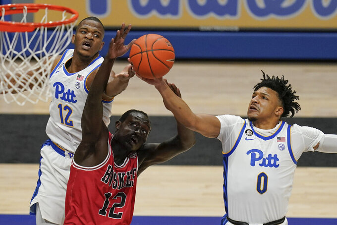 Pittsburgh's Ithiel Horton (0) gets a rebound in front of Northern Illinois' Zool Kueth, front left, and Pittsburgh's Abdoul Karim Coulibaly during the first half of an NCAA college basketball game Saturday, Dec. 5, 2020, in Pittsburgh. (AP Photo/Keith Srakocic)