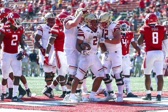 Boston College Eagles offensive lineman John Phillips (70) and offensive lineman Alec Lindstrom (72) celebrate with running back AJ Dillon (2) after he scored a touchdown in the fourth quarter of an NCAA college football game on Saturday, Sept. 21, 2019, in Piscataway, N.J. Boston College won, 30-16. (Andrew Mills/NJ Advance Media via AP)