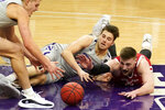 Wisconsin forward Micah Potter, right, battles for the ball against Northwestern forward Miller Kopp, left, and center Ryan Young during the first half of an NCAA college basketball game in Evanston, Ill., Saturday, Feb. 21, 2021. (AP Photo/Nam Y. Huh)