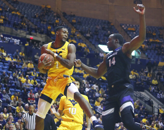 West Virginia forward Derek Culver (1) grabs a rebound while defended by Kansas State forward Makol Mawien (14) during the first half of an NCAA college basketball game Monday, Feb. 18, 2019, in Morgantown, W.Va. (AP Photo/Raymond Thompson)