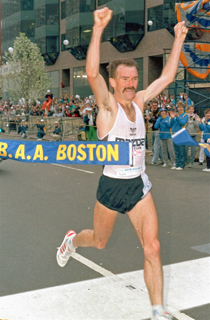 FILE - In this April 21, 1986, file photo, Rob de Castella of Australia breaks the tape to win the 90th running of the Boston Marathon in Boston. The Noosa Triathlon, which organizers say is the largest Olympic-format (1.5-kilometer swim, 40-kilometer cycle and 10-kilometer run) in the world was among the largest of more than 19,000 events canceled around Australia this year, with the loss of an estimated 11,000 jobs and more than 75 million Australian dollars ($54 million) lost to charities from money that is usually raised during the events. (AP Photo/David Tenenbaum, File)