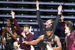 Florida State players cheer as their team breaks away from Miami during the first half of an NCAA college basketball game, Wednesday, Feb. 24, 2021, in Coral Gables, Fla. (AP Photo/Marta Lavandier)