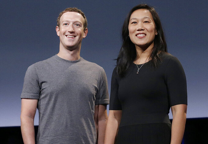 FILE- In this Sept. 20, 2016, file photo, Facebook CEO Mark Zuckerberg and his wife, Priscilla Chan, smile as they prepare for a speech in San Francisco. Facebook founder Mark Zuckerberg and his wife, Priscilla Chan, on Tuesday, Oct. 13, 2020, donated an additional $100 million to helping local election offices prepare for November even as some conservatives are stepping up their efforts to stop the funds from being used. (AP Photo/Jeff Chiu, File)