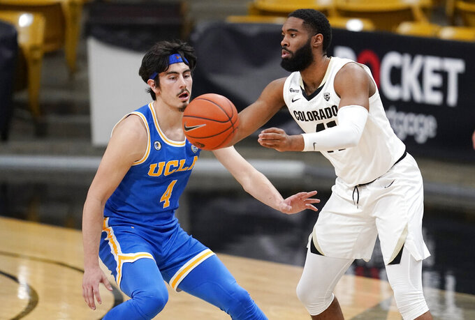 Colorado forward Jeriah Horne, right, passes the ball as UCLA guard Jaime Jaquez Jr. defends in the first half of an NCAA college basketball game Saturday, Feb. 27, 2021, in Boulder, Colo. (AP Photo/David Zalubowski)