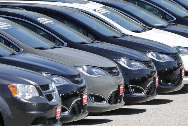 FILE - In this Wednesday, April 15, 2020 file photo, Cars are parked in an auto dealer lot in unincorporated St. Louis County, Mo. U.S. new vehicle sales fell 9.7% in the third quarter, but that's not all that bad for the auto industry. Consumers are paying record prices largely for loaded out trucks and SUVs. Discounts are down because vehicle supplies are limited. Interest rates are low.. (AP Photo/Jeff Roberson, File)