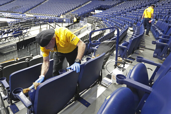 Luis Rivera, left, sanitizes seats in Bridgestone Arena after the remaining NCAA college basketball games in the Southeastern Conference tournament were cancelled Thursday, March 12, 2020, in Nashville, Tenn. The tournament was cancelled Thursday due to coronavirus concerns. (AP Photo/Mark Humphrey)