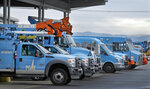FILE - In this Jan. 14, 2019, file photo, Pacific Gas & Electric vehicles are parked at the PG&E Oakland Service Center in Oakland, Calif. A federal judge is expected to approve pon Friday, June 19, 2020, Pacific Gas & Electric's $58 billion plan for ending its 17-month stint in bankruptcy, clearing the way for the nation's largest utility to begin paying $25.5 billion to cover the losses in a series of horrific wildfires ignited by its long-neglected electrical grid. (AP Photo/Ben Margot, File)