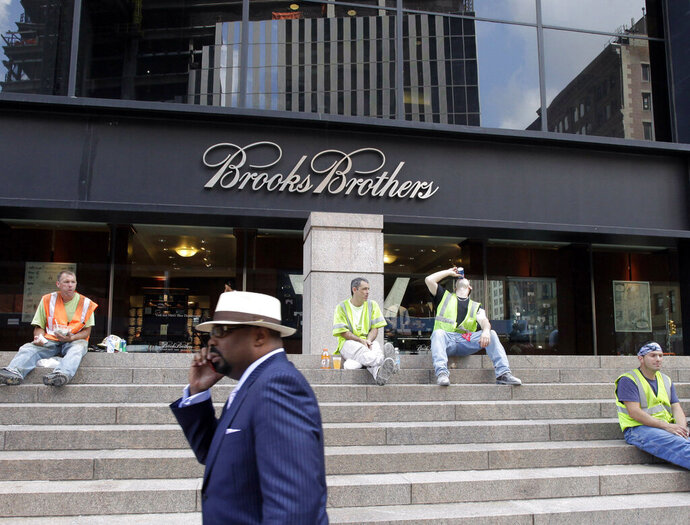CORRECTS DATE OF PHOTO TO AUG. 4, 2011, INTEAD OF SEPT. 11, 2001 - FILE - In this Aug. 4, 2011, file photo, a man passes a Brooks Brothers store on Church Street in New York's financial district. The 200-year-old fashion retailer that says it's put 40 U.S. presidents in its suits, is filing for bankruptcy protection on Wednesday, July 8, 2020. (AP Photo/Mark Lennihan, File)