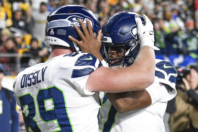 Seattle Seahawks tight end Will Dissly (89) celebrates with quarterback Geno Smith (7) after scoring a touchdown against the Pittsburgh Steelers during the second half an NFL football game, Sunday, Oct. 17, 2021, in Pittsburgh. (AP Photo/Don Wright)
