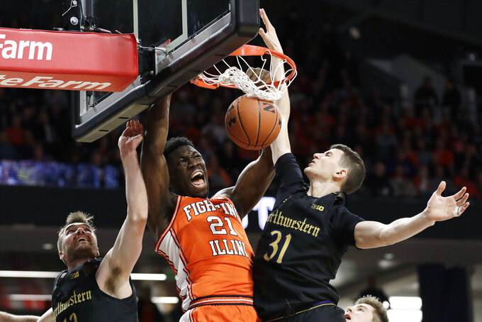 Illinois center Kofi Cockburn, center, dunks against Northwestern guard Pat Spencer, left, and forward Robbie Beran during the first half of an NCAA college basketball game in Evanston, Ill., Thursday, Feb. 27, 2020. (AP Photo/Nam Y. Huh)