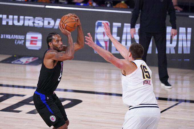 Los Angeles Clippers forward Kawhi Leonard (2) shoots over Denver Nuggets center Nikola Jokic (15) during the second half of an NBA conference semifinal playoff basketball game Tuesday, Sept. 15, 2020, in Lake Buena Vista, Fla. (AP Photo/Mark J. Terrill)