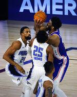 Philadelphia 76ers' Joel Embiid (21) scores against Orlando Magic's Khem Birch (24) and Wes Iwundu (25) during the second half of an NBA basketball game Friday, Aug. 7, 2020, in Lake Buena Vista, Fla. (Kevin C. Cox/Pool Photo via AP)