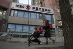 Residents pass by an Industrial and Commercial Bank of China (ICBC) branch in Beijing Tuesday, Jan. 19, 2021. Profit at state-owned companies that dominate China's banking, oil and most other industries rose by as much as 25% last year as the country recovered from the coronavirus pandemic, according to the. State-Owned Assets Supervision and Administration Commission which oversees 97 companies directly under the Cabinet including PetroChina Ltd., Asia's biggest oil producer; China Mobile Ltd., the world's biggest phone carrier by number of subscribers, and Industrial and Commercial Bank of China Ltd., the world's biggest bank by assets. (AP Photo/Ng Han Guan)