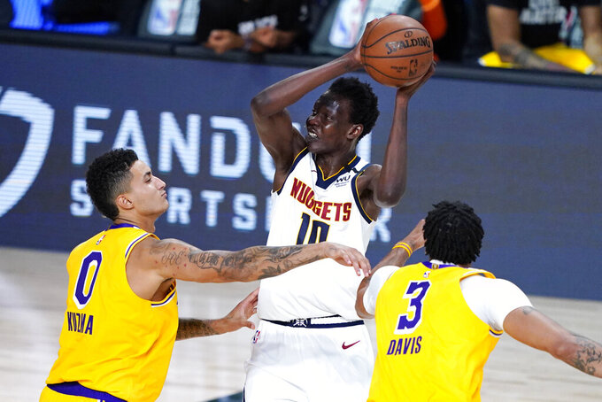 FILE - Denver Nuggets' Bol Bol (10) is pressured by Los Angeles Lakers' Kyle Kuzma (0) and Anthony Davis (3) during the second half of an NBA basketball game in Lake Buena Vista, Fla., in this Monday, Aug. 10, 2020, file photo. It's understandable if names such as skateboarder Sky Brown, Denver Nuggets center Bol Bol or French Open champion Iga Swiatek don't ring an instant bell. Just wait, though. By the time 2021 ends, they could be making an even bigger name for themselves. (AP Photo/Ashley Landis, Pool, File)