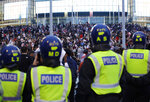 A line of police watch supporters outside Wembley Stadium in London, Sunday, July 11, 2021, during the Euro 2020 soccer championship final match between England and Italy. (AP Photo/David Cliff)