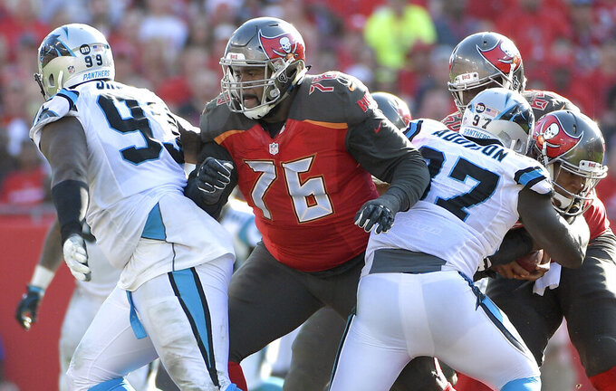 FILE - In this Jan. 1, 2017, file photo, Tampa Bay Buccaneers offensive tackle Donovan Smith (76) blocks between Carolina Panthers defensive tackle Kawann Short (99) and defensive end Mario Addison (97) during the second half of an NFL football game in Tampa, Fla. The Buccaneers have re-signed Smith to a three-year, $41.25 million contract, the team announced Tuesday, March 5, 2019. (AP Photo/Phelan M. Ebenhack, File)