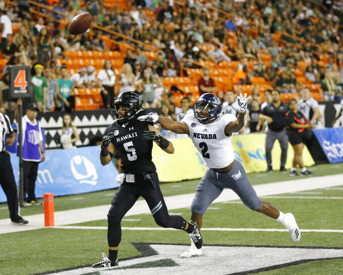 While being guarded by Nevada defensive back Asauni Rufus (2), Hawaii wide receiver John Ursua (5) can't catch an overthrown pass in the end zone during the third quarter at an NCAA college football game Saturday, Oct. 20, 2018, in Honolulu. (AP Photo/Marco Garcia)