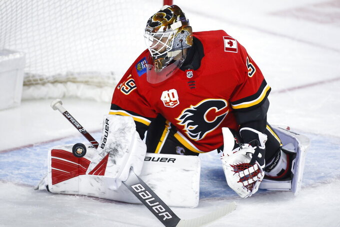 FILE - In this Jan. 28, 2020, file photo, Calgary Flames goalie Cam Talbot deflects a shot during the second period of an NHL hockey game against the St. Louis Blues in Calgary, Alberta. The former Flames goalie signed an $11 million, three-year deal with the Minnesota Wild.  (Jeff McIntosh/The Canadian Press via AP, File)